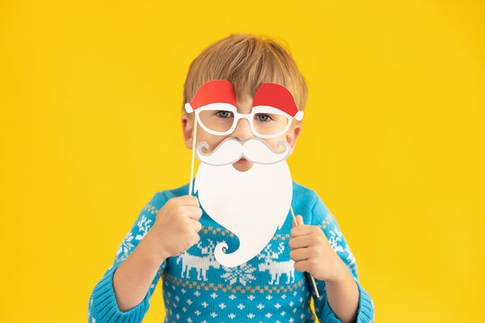 Happy child holding Santa Claus hat and beard