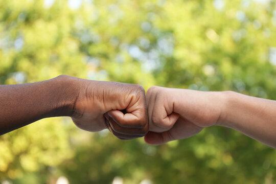 Men making fist bump outdoors, closeup view