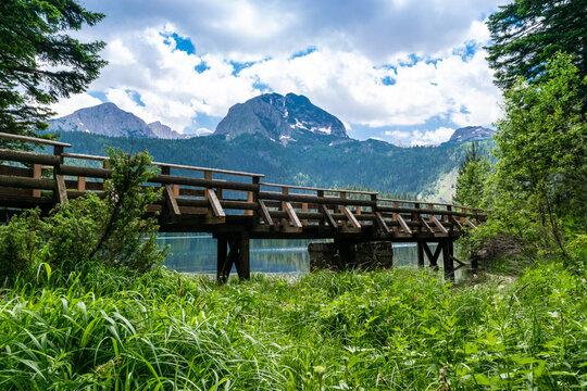 Wooden footbridge over stream against background of Meded Peak and Glacial Black Lake. Durmitor National Park. Montenegro.