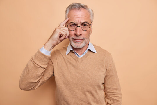Serious mature bearded man keeps finger on temple tries to recall something in mind focused at camera wears spectacles casual jumper isolated over brown background. People age and thoughts concept