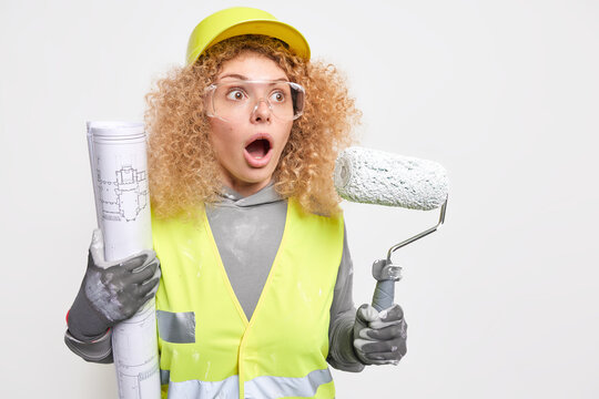 Stupefied professional female construction worker stares with shock cannot believe her eyes keeps mouth wide opened works on interior of new apartment uses architectural blueprint and paint roller