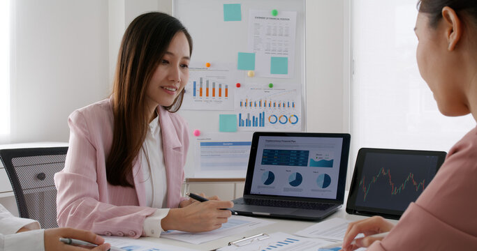 Group asia woman people talk in budget plan report, brief idea on chart graph data in paper work on laptop tablet at office desk table teach in tax loan consult career class, stock broker, trader job.