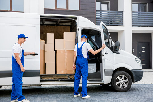 Two removal company workers unloading boxes from minibus into new home