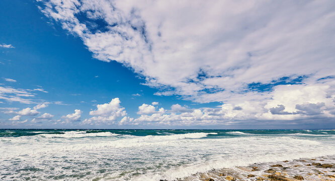 Ocean with waves and blue sky with clouds.