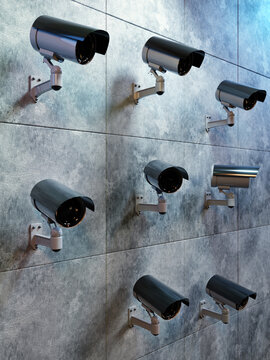 Many security cameras mounted to the wall monitoring the area