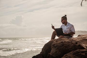 Cyfrowy nomada, człowiek pracujący z laptopem i smartfonem zdalnie na tle oceanu i skał siedzący na wybrzeżu.