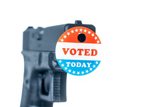 Concept for election violence with handgun decorated with I voted today sticker with hole made by fired bullet