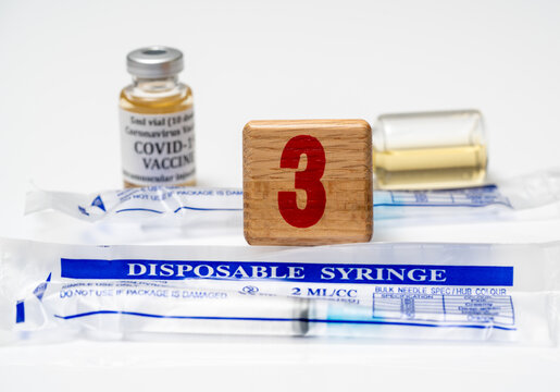 Booster shot for mRNA vaccines for Covid-19 with wooden block with number three with disposable syringes ready to enhance protection against virus