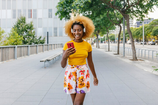 Happy young hispanic woman using mobile phone while listening to music and walking in the street - Millennial generation lifestyle concept