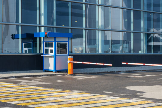 Barriers next to building. Automobile barriers. Concept is checkpoint system for cars. Yellow and white crosswalk. System of admitting cars to business center. Two automatic barriers