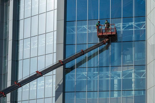 Workers are washing walls of building. Two men on boom of tower crane. Window cleaners at work. Workers wash glass skyscraper. Concept - building cleaning services. Window cleaning company employees