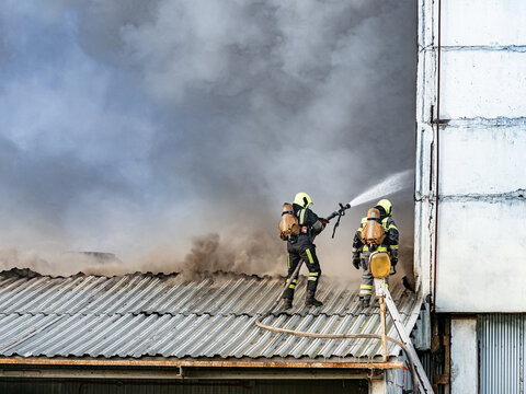 Fire fighting. Firefighters spray water towards smoke. Fire service workers on roof of building. Concept - extinguishing industrial facilities. Firefighters extinguish fire with water.