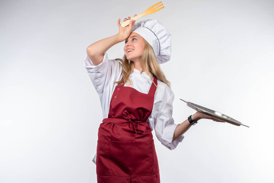 Happy woman cook. Girl cook on light background. Chef with empty tray and spatula. Young satisfied employee of restaurant. Chef with kitchen utensils.  girl cook smiles. Blond baker woman