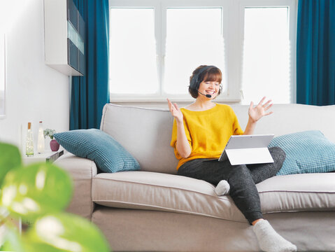 young beautiful woman using a laptop computer at home on sofa. online shopping and video call