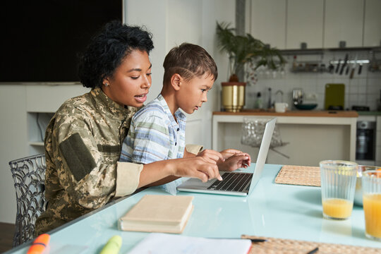 Military woman typing at the laptop keyboard while her little son sitting at her laps