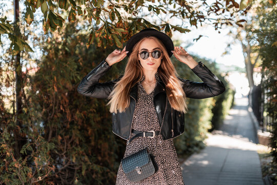 Stylish beautiful girl with sunglasses and a hat in a fashionable dress with a leather jacket and a black handbag walks near the autumn foliage in the city