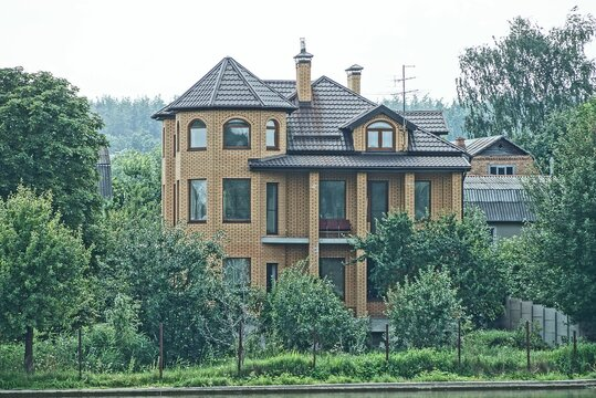 large brown brick private house among green vegetation and trees on the street