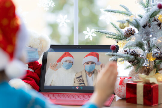 Happy child wearing medical mask in video chat. Christmas holiday