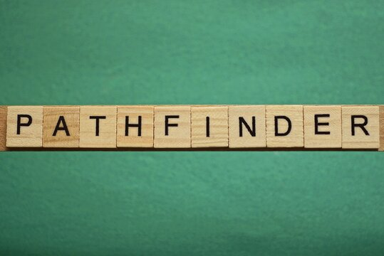 gray word pathfinder from small wooden letters on a green table