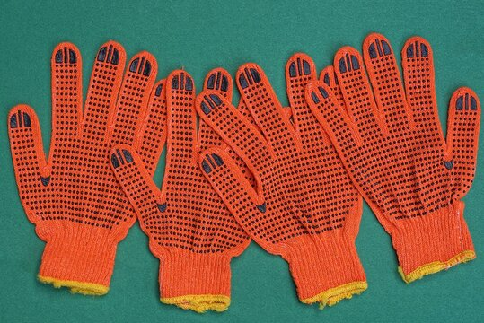 four red work gloves made of fabric lies on a green table