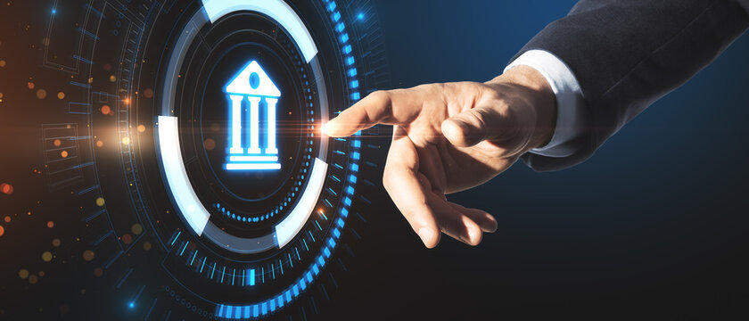Businessman hand pointing at creative glowing blue public building hologram on dark background. Business, finance and online banking concept.