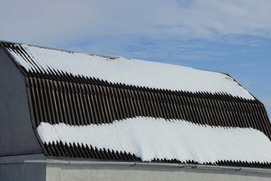 gray slate roof of a private house under white snow on a winter street against a blue sky