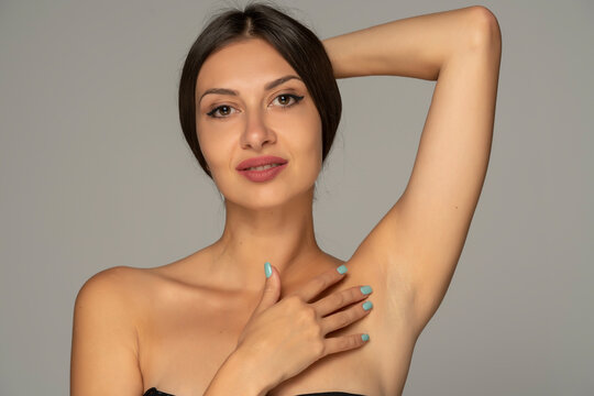 young smiling woman caressing the armpit with her fingers