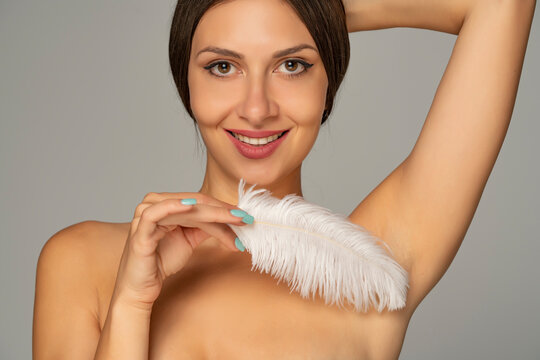 young smiling woman caressing the armpit with white feather