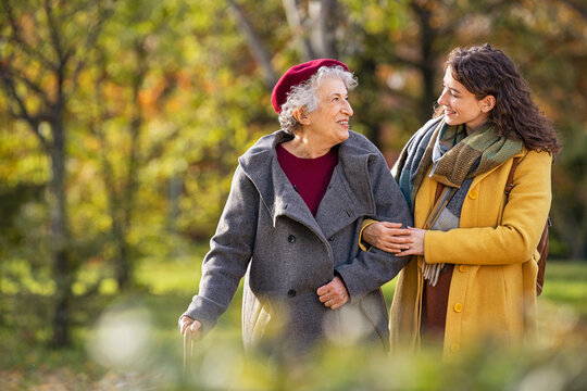 Senior woman walking with granddaughter in park during autumn