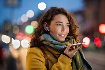 Fototapeta Woman sending voice note on city street in winter night obraz