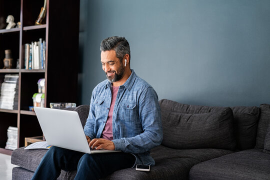 Indian man typing on laptop while working from home