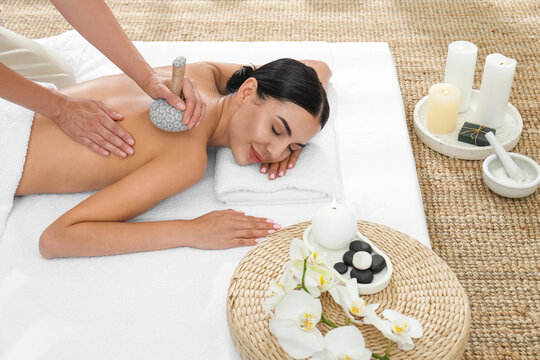 Young woman receiving herbal bag massage in spa salon