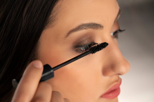 young woman applied mascara to her lashes