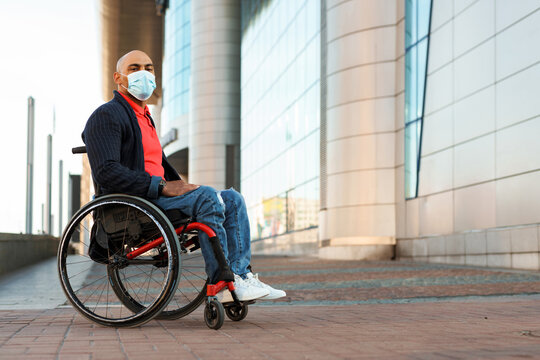 Man wearing face mask looking at camera while sitting in wheelchair