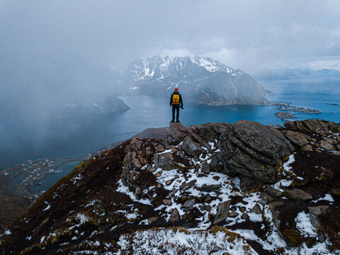 Hiker with backpack enjoying sunset landscape in Lofoten Norway