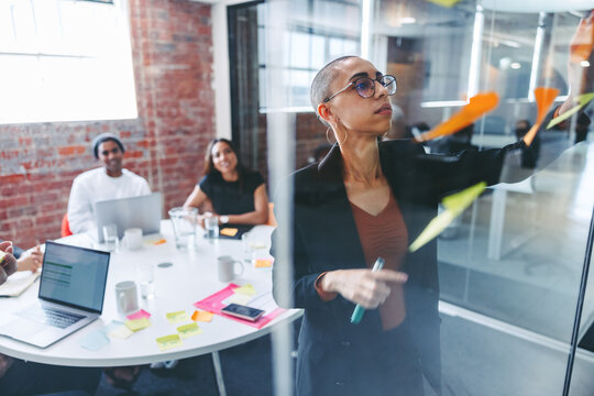 Focused young businesswoman sticking adhesive notes to a glass w