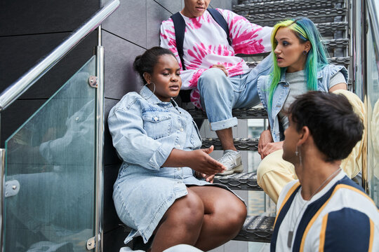 Friends sitting on metal stairs and talking