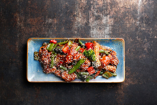 Thai chicken dish, on a blue plate, on a black stony background, top view. Breaded chicken breast pieces, stir fried with vegetables and sesame in a spicy sweet sauce. Honey chilli chicken.