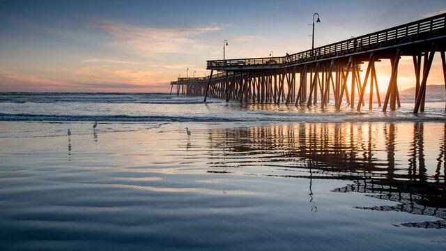 Beautiful sunset through the pedestrian bridge at Pismo beach pier, California, USA. Summer vacation concept