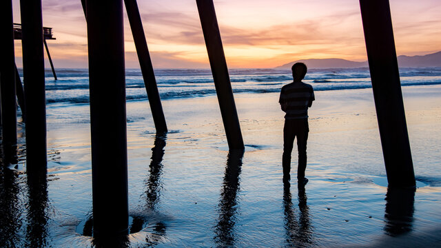 Silhouette shot of tourist man looking at beautiful sunset under bridge structure of Pismo pier at Pismo beach, California, USA. Summer vacation travel concept
