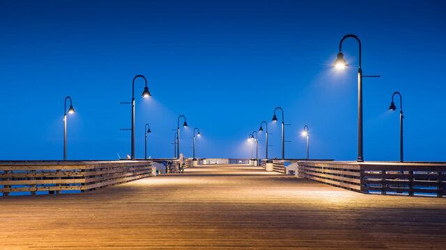 Empty wooden pedestrian bridge with illuminated street light during twilight time at Pismo beach pier. West coast tourist attraction in California, USA.
