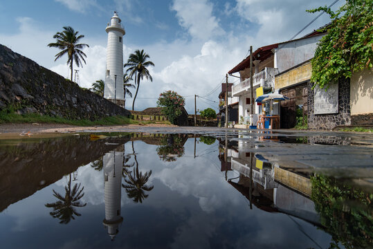 White lighthouse and plam trees reflected on the street in Galle Fort, Sri Lanka.