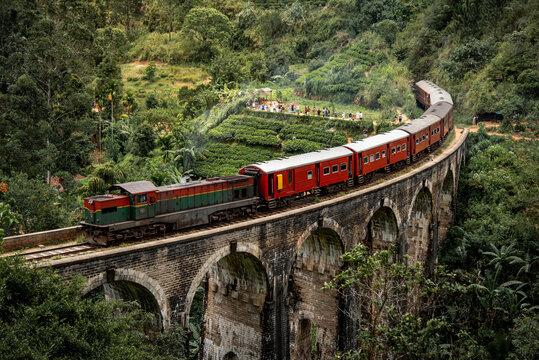 Red classic train on Nine arches bridge, running over ceylon tea plantation in Ella. Famous tourist attraction of Sri Lanka.