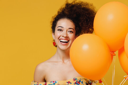 Young happy smiling woman with culry hair in casual clothes celebrating birthday holiday party hold bunch of colorful air inflated helium balloons isolated on plain yellow background studio portrait