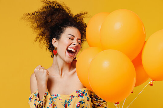 Young happy woman with culry hair in casual clothes celebrating birthday holiday party hold bunch of colorful air inflated helium balloons do winner gesture isolated on plain yellow background studio.