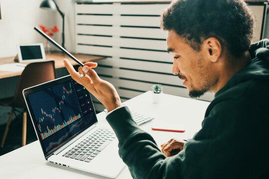 Investing in stock exchange market. Black man working remote using laptop