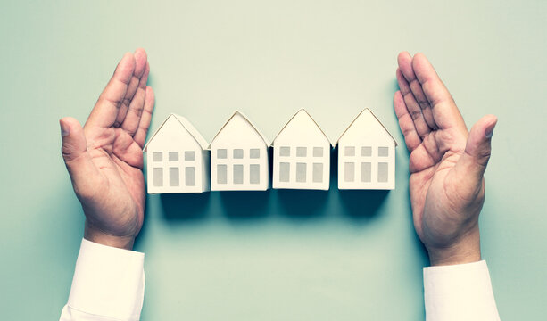 Business property,real estate and investment concepts with investor hand and white model house
