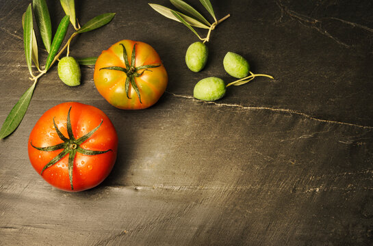 Still life with two organically grown tomatoes and olives, symbols of the Mediterranean diet, on a dark background with copy space to the right of the image.