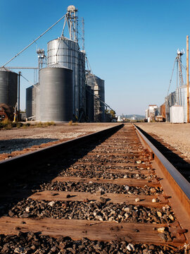 Several Tall Steel Grain Silos for Storing Crops and Railroad Tracks for Transport