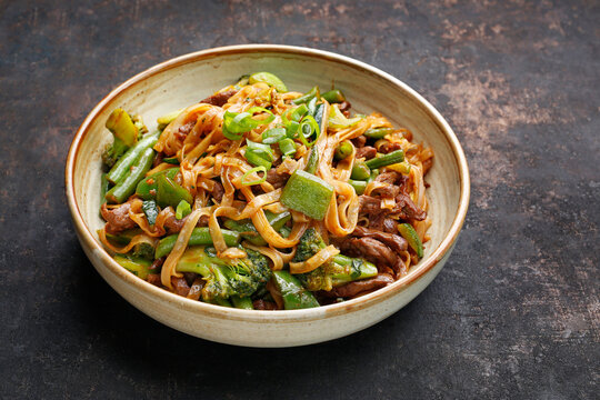 Close up of oriental noodles in a bowl, on black stony background. Beef fried on a wok with rice noodles, green beans, zucchini, pak choi and green peppers in spicy soy-oyster sauce. Thai cousine dish